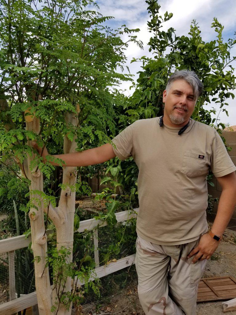 """6'2"""" tall husband next to one of the moringa tree."""